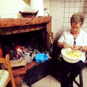 Elsa descascando batatas à lareira